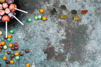Halloween trick or treat sweets lying on grey surface