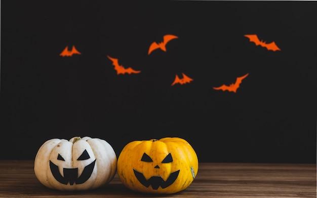 Хэллоуин две тыквы на деревянный стол. черный фон.