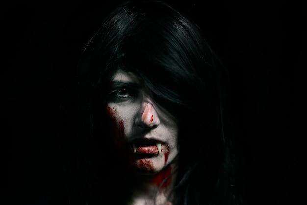 黒の上のハロウィーンの吸血鬼の美しい女性