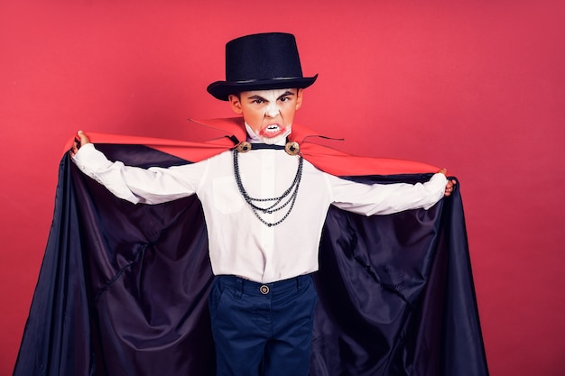 Halloween vampire boy waves his black, red cloak with his hands surrounded on red studio background. kid vampire makeup.