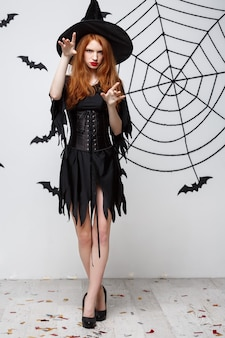 Halloween witch concept  fulllength halloween witch casting spells with serious expression over dark grey  wall with bat and spider web