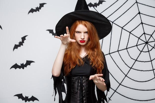 할로윈 마녀 개념 전장 할로윈 마녀는 박쥐와 거미줄이 있는 짙은 회색 벽 위에 진지한 표정으로 주문을 캐스팅합니다.