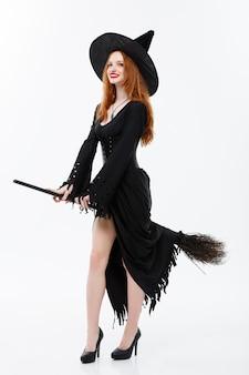 白い壁の上のハロウィーンパーティーを祝うためのほうきでハロウィーンの魔女の概念の完全な長さの幸せなエレガントな魔女