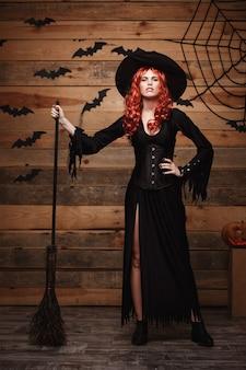 ハロウィーンの魔女のコンセプトフルレングスの幸せなハロウィーンの赤い髪の魔女が魔法のほうきでポーズをとっています...