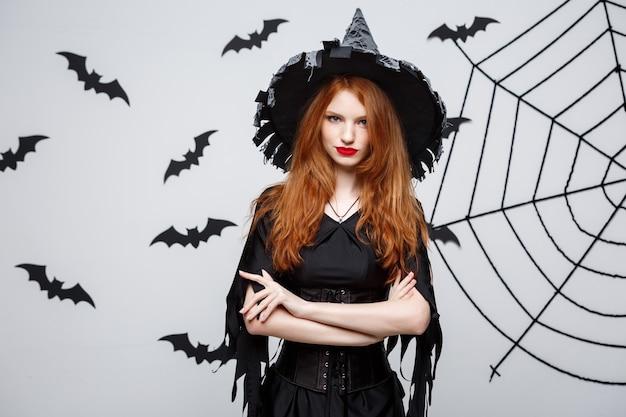 할로윈 마녀 개념 할로윈 마녀는 박쥐와 거미줄이 있는 짙은 회색 벽 위에 진지한 표정으로 포즈를 취하고 있습니다.