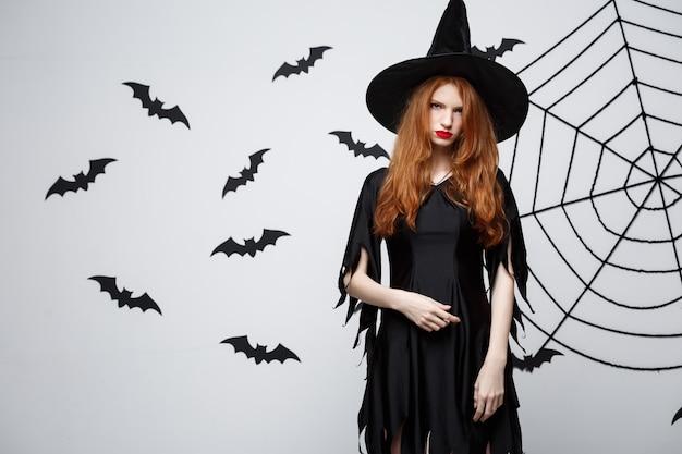 ハロウィーンの魔女のコンセプトハロウィーンの魔女は、バットとクモの巣で暗い灰色の壁に真剣な表情でポーズを保持しています