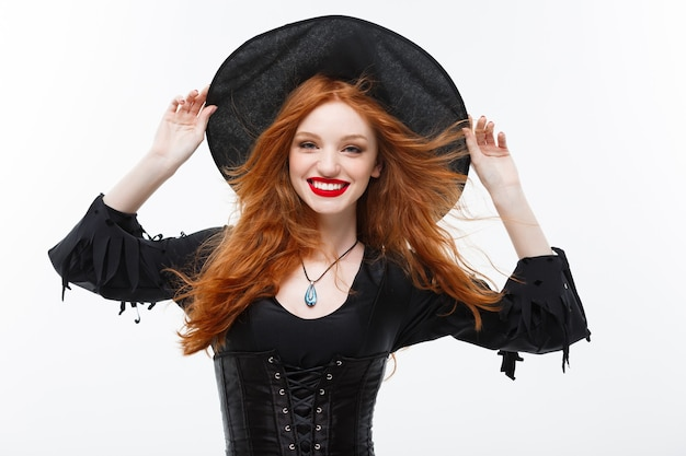 Halloween witch concept - happy halloween ginger hair witch. isolated on white wall.