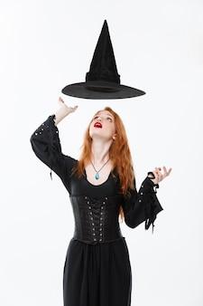 ハロウィーンの魔女のコンセプト-魔法の帽子が頭上を飛んでいるハッピーハロウィーンのセクシーな生姜髪の魔女。白い壁に隔離。