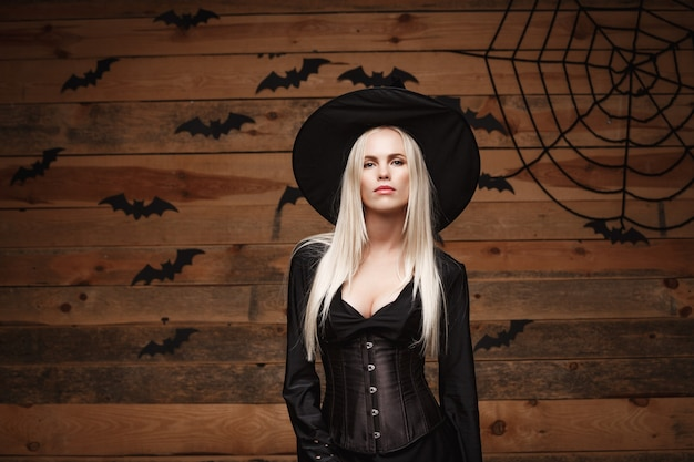 古い木製のスタジオの背景の上にポーズを保持しているハロウィーンの魔女の概念幸せなハロウィーンのセクシーな魔女