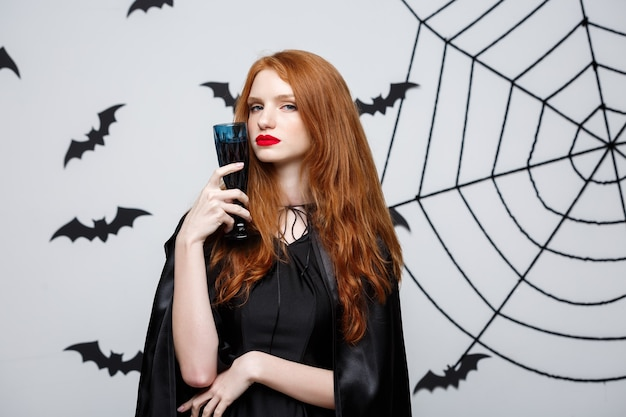 Halloween witch concept - happy halloween witch holding glass of bloody red wine over dark grey  wall with bat and spider web.