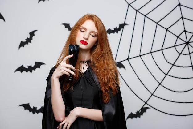 Concetto di strega di halloween - strega di halloween felice che tiene in mano un bicchiere di vino rosso sanguinante su un muro grigio scuro con pipistrello e ragnatela.
