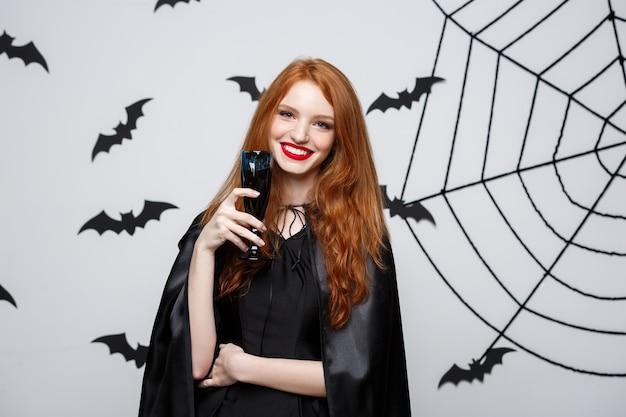 Концепция ведьмы хэллоуина - счастливая ведьма хэллоуина, держащая бокал кровавого красного вина над темно-серой стеной с летучей мышью и паутиной.