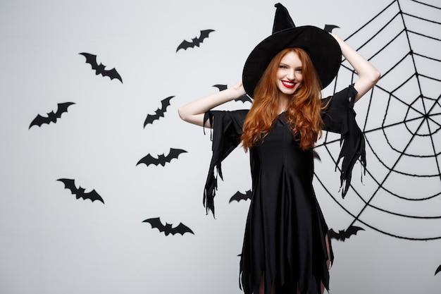 할로윈 마녀 개념 해피 할로윈 마녀는 박쥐와 거미줄이 있는 짙은 회색 벽 위에 포즈를 취하고 있습니다.