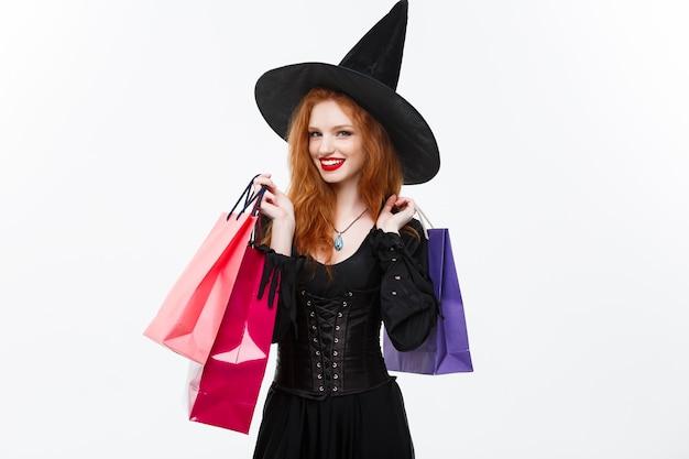 Concetto della strega di halloween strega felice di halloween che sorride e che tiene i sacchetti della spesa variopinti sulla parete bianca