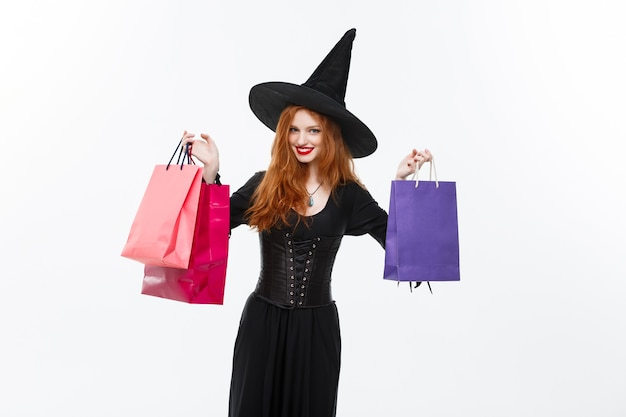 Halloween witch concept  happy halloween witch smiling and holding colorful shopping bags on white wall