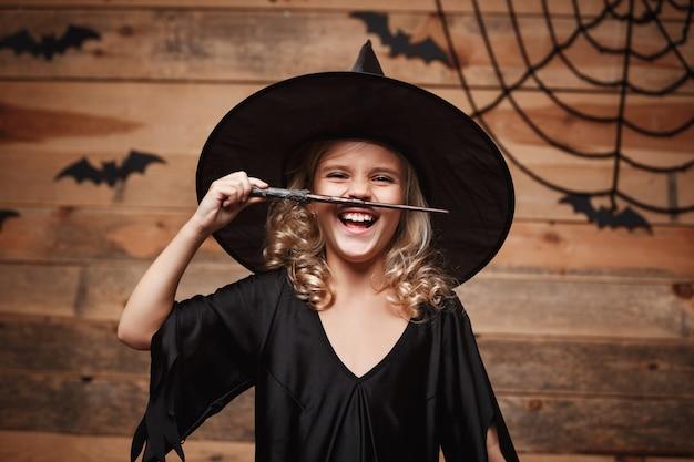 ハロウィーンの魔女のコンセプト-小さな魔女の子供は魔法の杖で遊ぶのを楽しんでいます。バットとクモの巣の背景の上。
