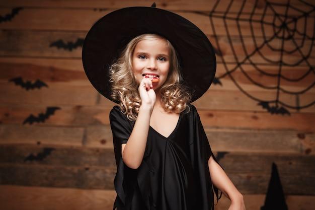 ハロウィーンの魔法の概念 - ハロウィーンの甘い甘いキャンデーと明るい笑顔の小さな魔女。バットとスパイダーウェブの背景。