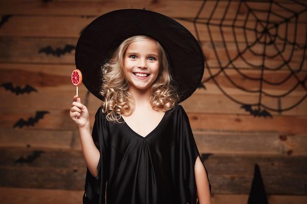 ハロウィーンの魔女のコンセプト-陽気な笑顔でハロウィーンの甘いとキャンディーを持つ小さな魔女の子供。バットとクモの巣の背景の上。