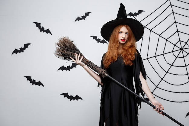 Halloween witch concept  portrait of beautiful young witch with broomstick over grey wall with bat and spider web wall