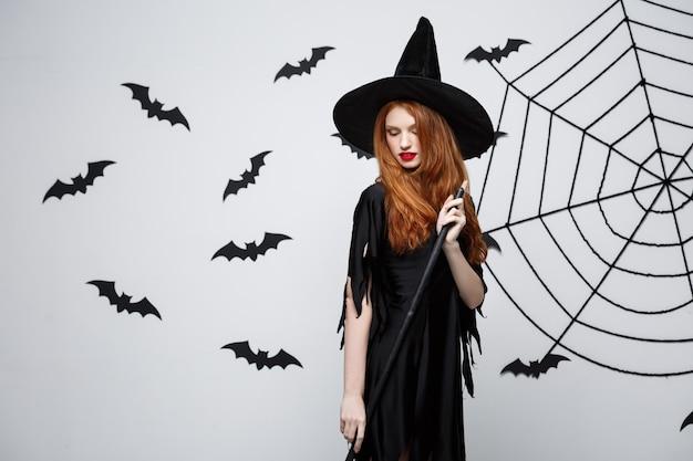 Halloween strega concetto ritratto di bella giovane strega con manico di scopa sul muro grigio con pipistrello e ragnatela wall