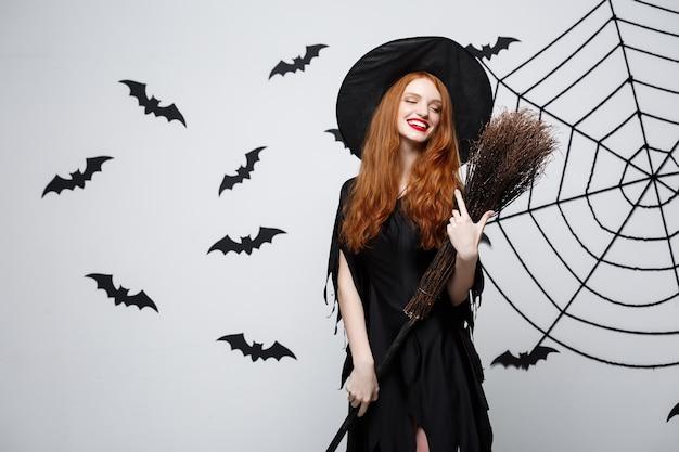 バットとクモの巣の壁と灰色の壁にほうきで美しい若い魔女のハロウィーンの魔女の概念の肖像画