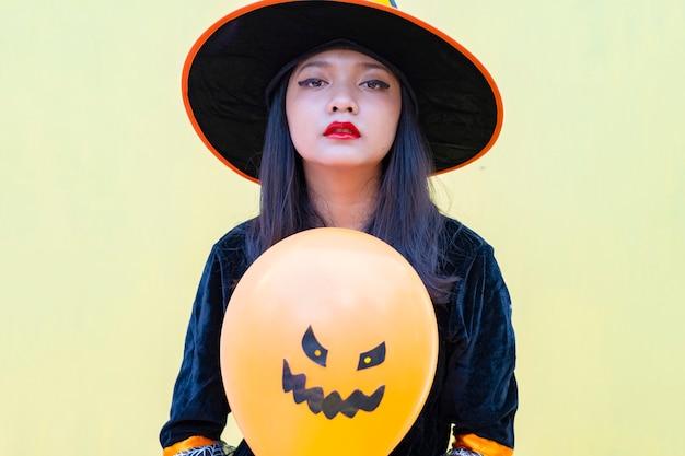 ハロウィーンの魔女は黄色の背景に風船を保持します。