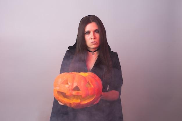 Halloween witch holding a orange pumpkin jack o lantern with smoke