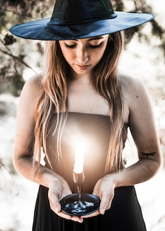 Strega di halloween guardando il candelabro nella foresta di sole