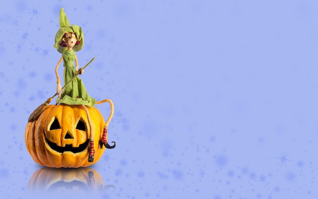 Halloween witch sit on carved pumpkin