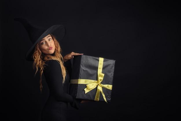 선물 상자를 들고 검은 벽에 검은 모자와 할로윈 마녀