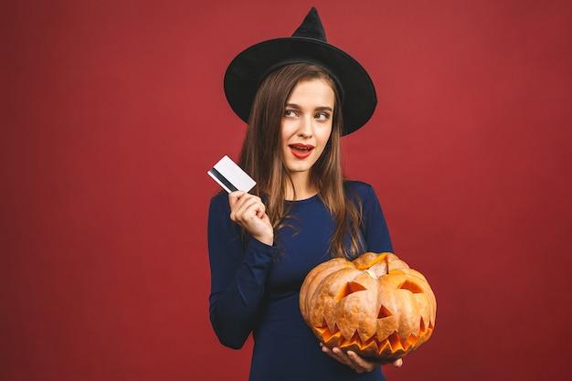 切り分けられたカボチャとクレジットカード-赤の背景に分離されたハロウィーンの魔女。ハロウィーンの衣装の感情的な若い女性。
