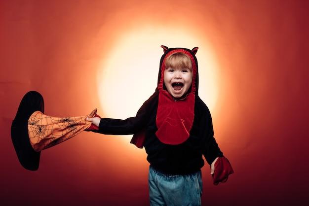暗い森の中で刻まれたカボチャと魔法のライトを持つハロウィーンの魔女。子供たちはカボチャで遊んで扱います。ハロウィンドレスと魔女の衣装と魔女の帽子。幸せなハロウィーン。