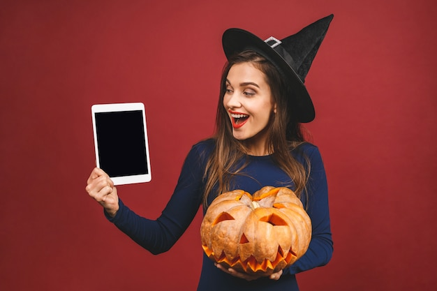 ハロウィーンの魔女の彫刻が施されたカボチャとタブレットの画面-赤の背景に分離。ハロウィーンの衣装の感情的な若い女性。