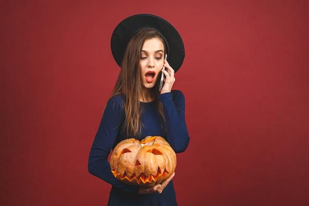 Хэллоуин ведьмы с резными тыквы - изолированные на красном фоне. эмоциональная молодая женщина в костюме хэллоуина. с помощью телефона.