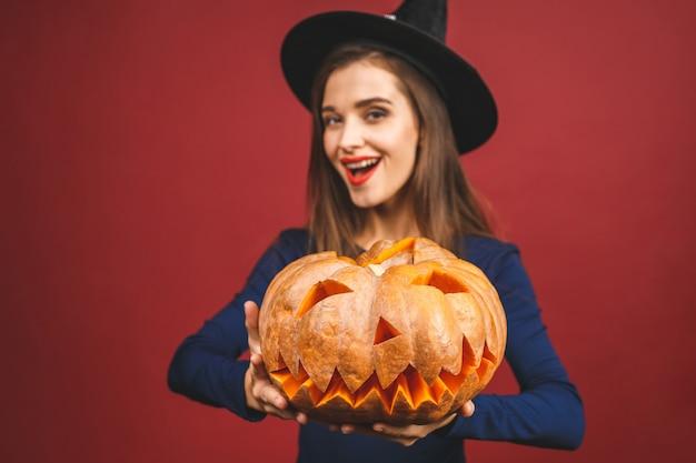 切り分けられたカボチャ-赤の背景に分離されたハロウィーンの魔女。ハロウィーンの衣装の感情的な若い女性。