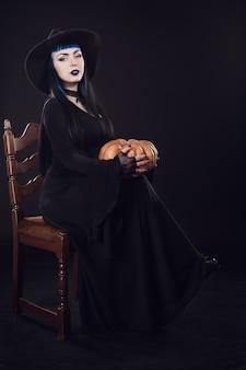 ハロウィン魔女と魔法のカボチャ。魔女の帽子と保持している衣装の美しい若い女性には、ジャックランタンカボチャが刻まれています。ハロウィンアートデザイン