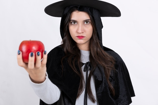 Halloween witch with apple on white background.