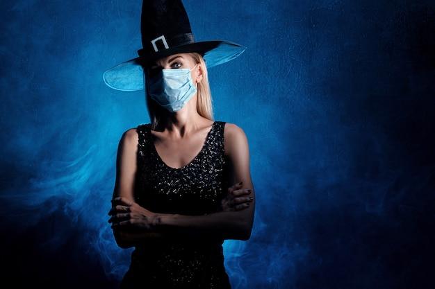 Ведьма на хэллоуин с черной шляпой и маской для лица