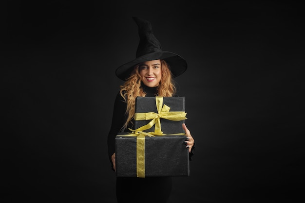 Halloween witch with a black hat on a black wall holding gift boxes