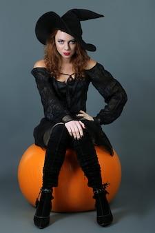 Ведьма хэллоуина с метлой на сером