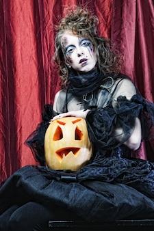 Ведьма на хэллоуин с резной тыквой на красной ковровой дорожке