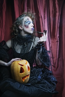 Ведьма на хэллоуин с резной тыквой над красной занавеской