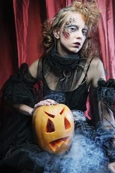 Ведьма на хэллоуин с резной тыквой над красными шторами