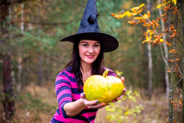 Halloween witch with a magic pumpkin in a dark forest. beautiful young woman in witches hat and costume holding carved pumpkin. halloween