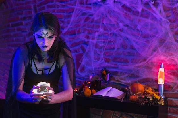 ハロウィーンの魔女、クモの巣の上に魔法のボールを持っているウィッカを装った若い女性