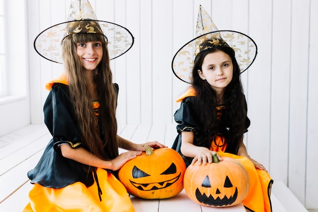 Halloween witches with spooky pumpkin on celebration