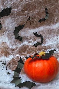 白いクモの巣の背景にカボチャ、クモ、クモの巣、コウモリとハロウィーン。ハロウィーンパーティーのコンセプト。縦の写真