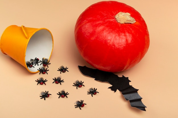カボチャ、クモ、黄色のバケツ、ハエ、ベージュの背景にコウモリとハロウィーン。ハロウィーンパーティーのコンセプト