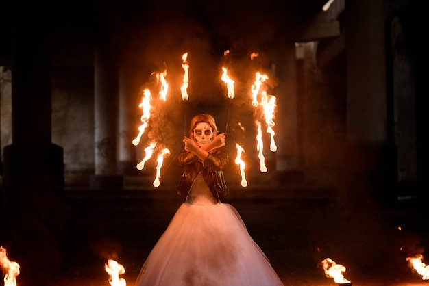 Halloween. young beautiful girl with make-up skeleton on her face with fire in her hands.