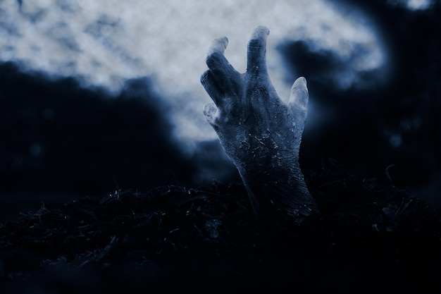 Halloween  zombie hand on dramatic dark cloud background.